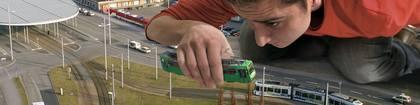 symbolhaftes Bild: Bauingenieur kniet vor Straßenbahngleisen und setzt eine Straßenbahn auf das Gleis
